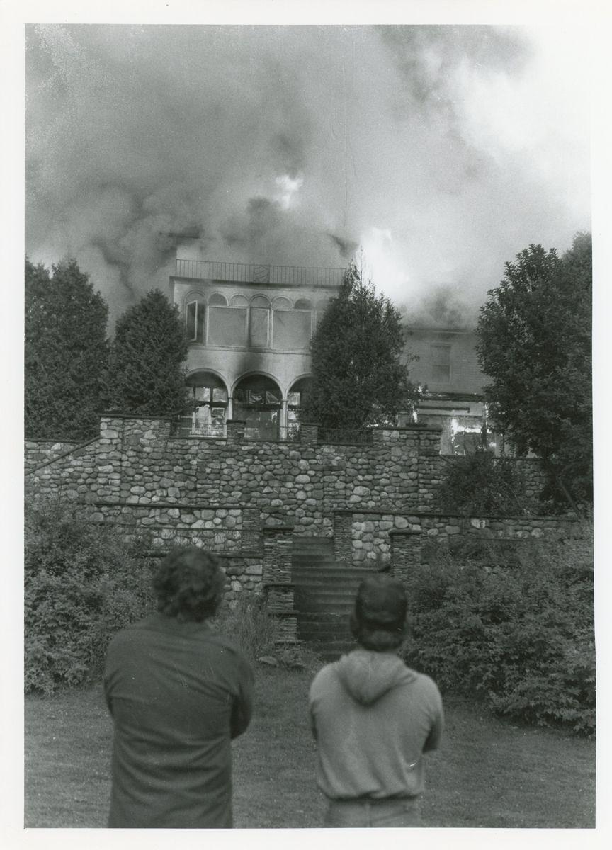 Two look on as Kaelber Hall is engulfed in flames, photograph, July 25, 1983